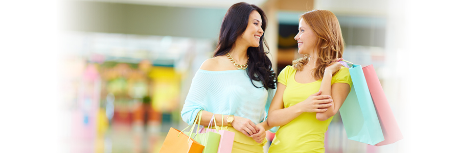 Two happy woman in mall holding shopping bags, QuickBooks and bookkeeping for Retail Stores in Lake City, FL and Gainesville, FL
